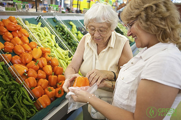 woman with senior citizen in the produce aisle