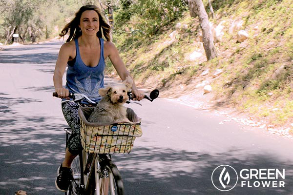 Mandee riding her bike with a dog in the basket