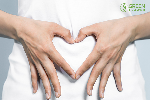 Hands forming heart shape over stomach