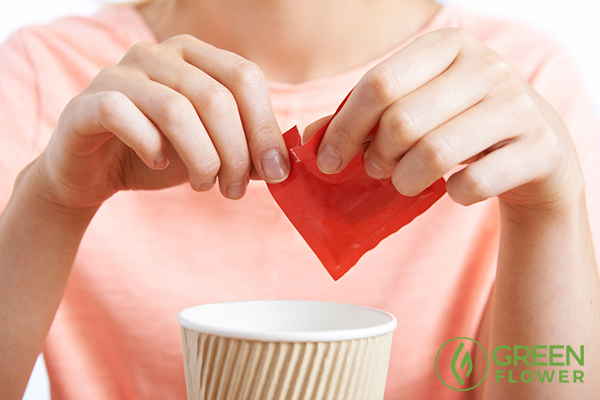woman adding sweetner in cup