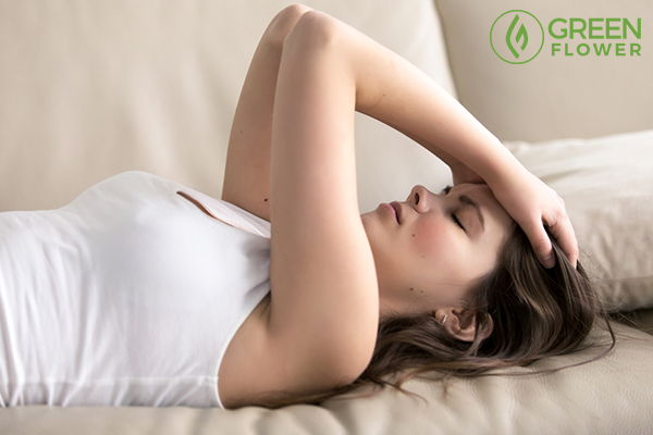 woman lying on sofa having headache